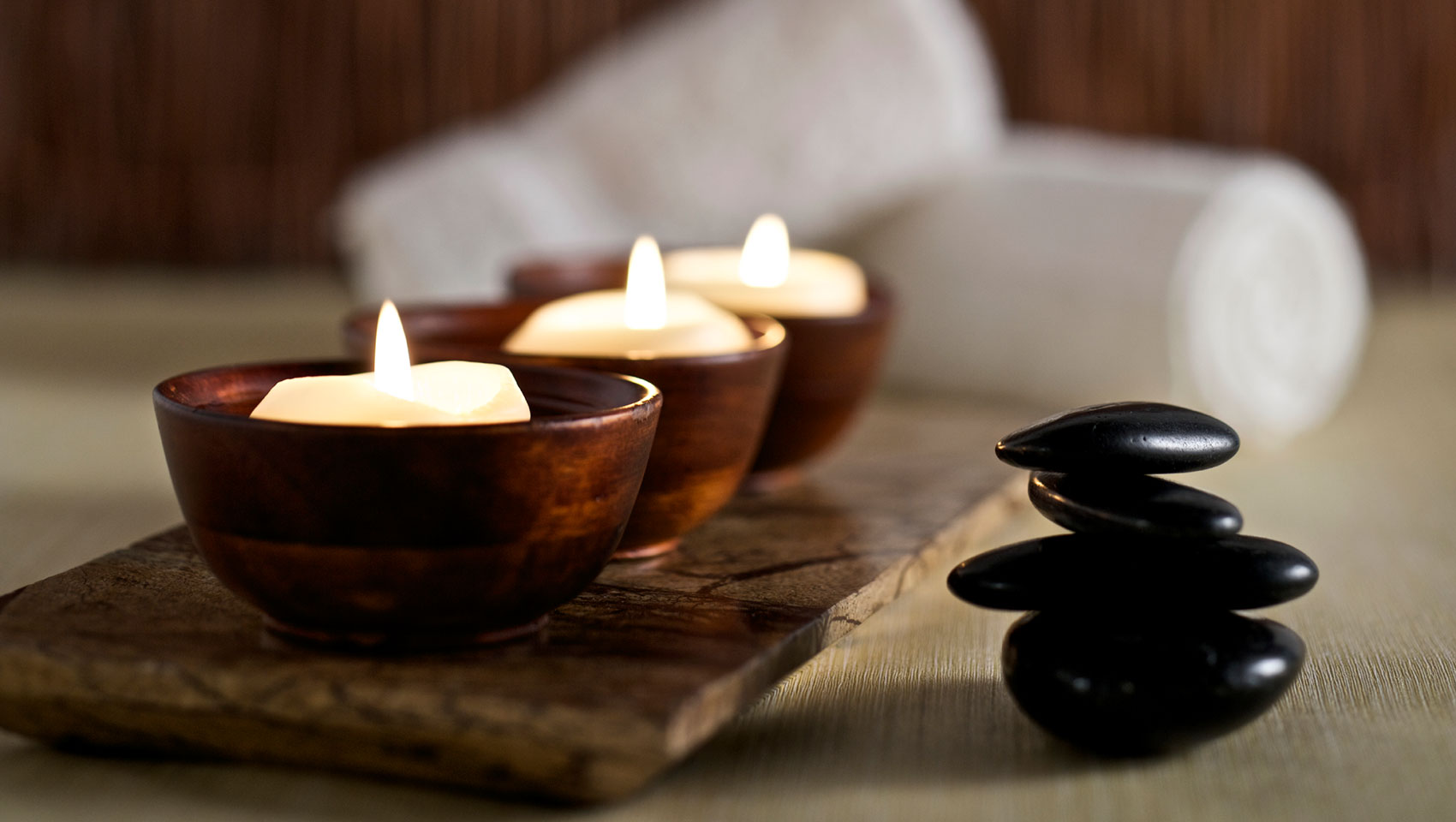 Hot Massage Stones, Burning candle in teakwood with towels rolled in the background