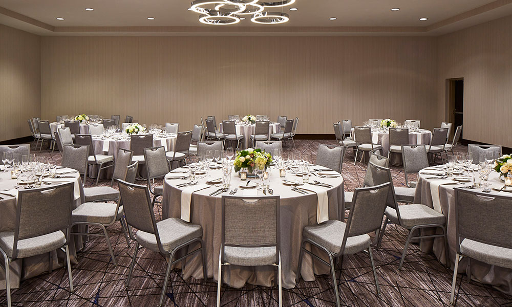 The Ballroom, light brown and gray undertones, set with round tables for a wedding