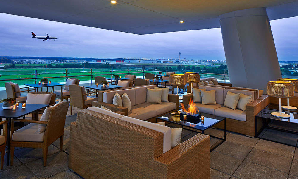 Outdoor rooftop lounge with plane taking off in the background